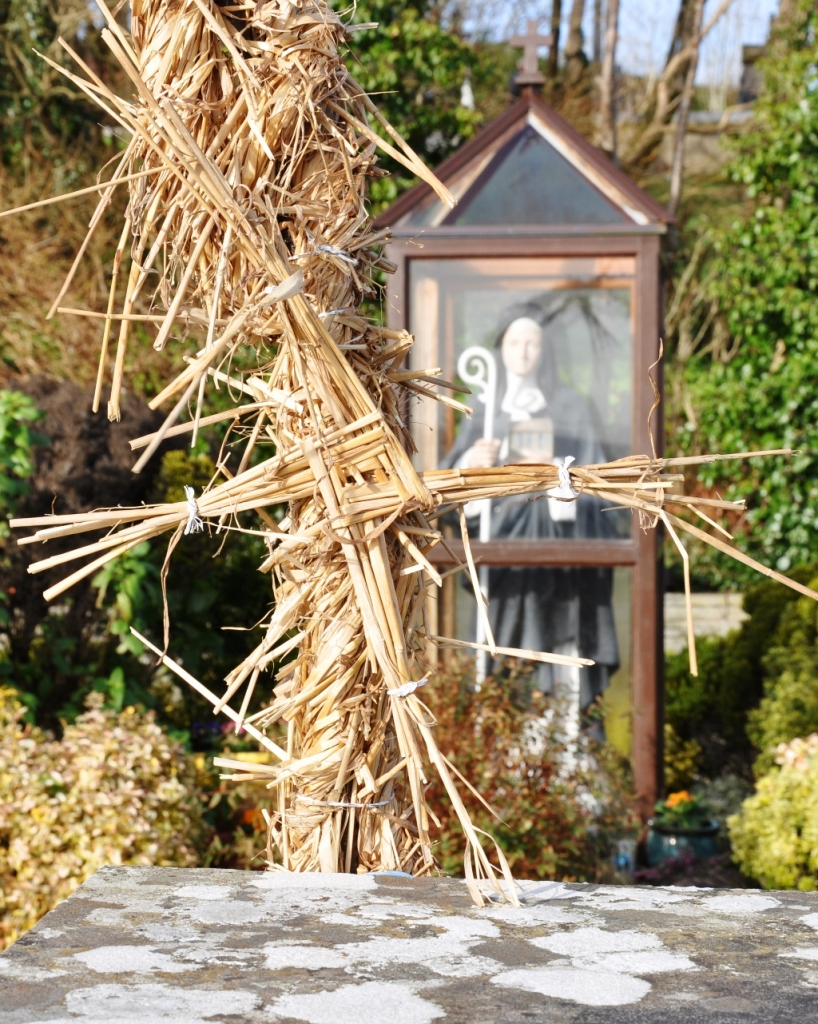 An hay arch (hay wrapped over a metal frame) covers the entrance to the well, it is adorned with St Brigid's Crosses