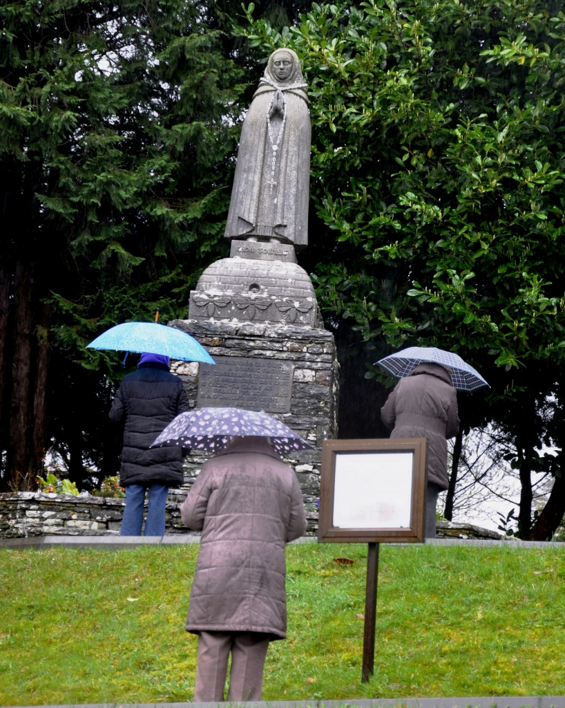 Pilgrims praying in the rain at the statue of St Gobnait