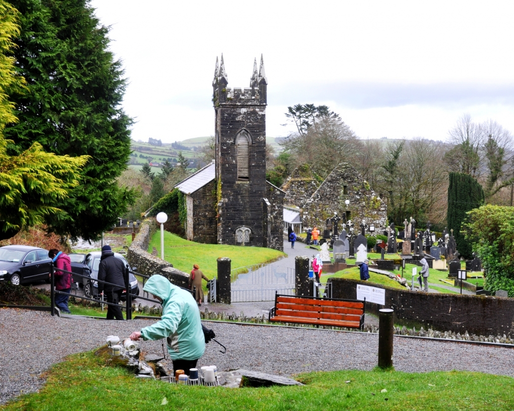 Looking down on the pilgrimage site from beside the statue. On of the wells is in the foreground, with the grave in the middle ground to the right and the old church, which is also part of the rounds, is in the background.