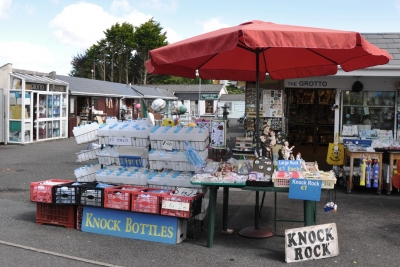 Stalls selling holy items in Knock a Marion apparition pilgrimage in the West of Ireland. It shows an intermixing of the sacred and the profane.