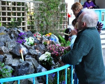 People praying and leaving votive offerings, especially candles and flowers, at the grotto