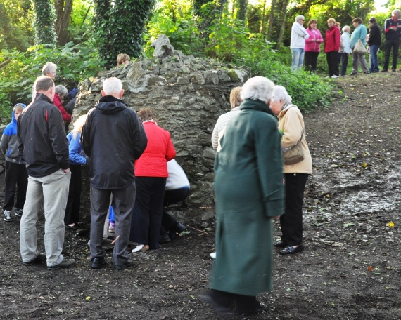 Pilgrims gathering around the well to collect water after the service.