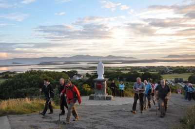 Pilgrims pass the statue of St Patrick as they begin their ascent, just after dawn.