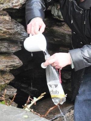 A woman collecting holy water at St Gobnait's holy well, Ballyvourney, on 11 Feb 2013, St Gobnait's Day.