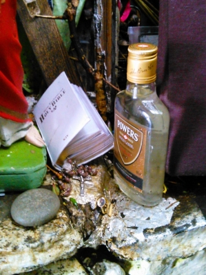 A small bible (wettened from the exposed spae above the well), with rosary beads inside, sits next to a whiskey bottle filled with some of the (presumably) well water.  The rest bwetween a statue of the Sacred Heart of Jesus and a cushion.