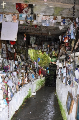 The vast collection of offerings which fill the grotto leading to the well.